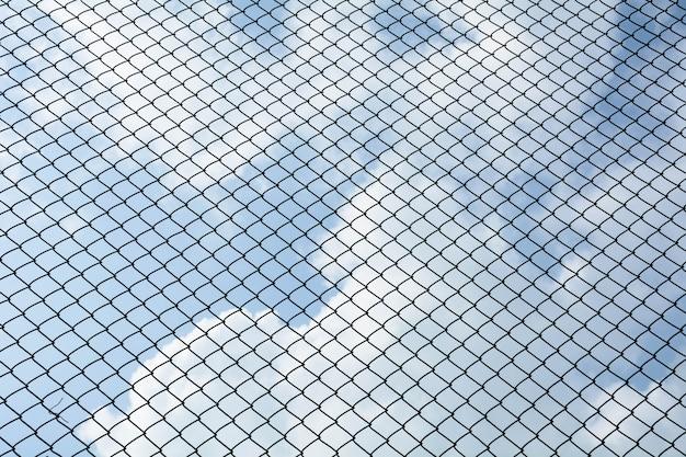 Het net van het kooimetaal op blauwe hemelachtergrond - patroonstijl