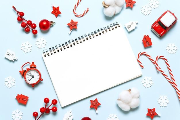 Het nieuwe concept dat van de vakantiekerstmis van de jaarwinter in notitieboekje met giften en decor op blauwe achtergrond schrijft