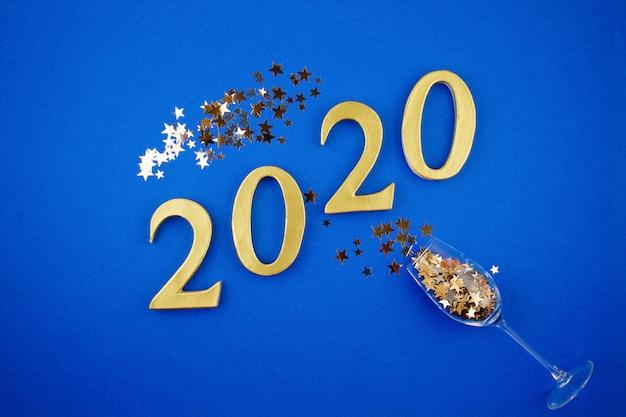 Het nieuwe concept van de jaarviering met champagneglas en confettien over de blauwe achtergrond