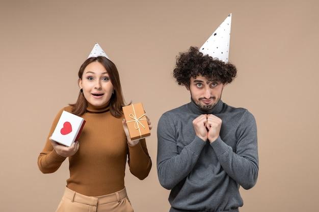 Het nieuwe jaarconcept met het gelukkige jonge paar draagt het emotionele meisje van de nieuwjaarshoed met hart