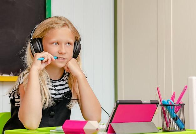 Het nieuwsgierige blondemeisje met oortelefoons is bij huisonderwijs. online cursus en onderwijsconcept