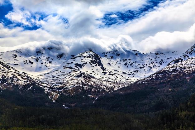 Het noorse landschap: besneeuwde berg in wolken