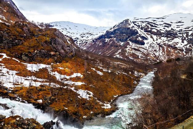 Het noorse landschap: rivier die tussen bergen stroomt
