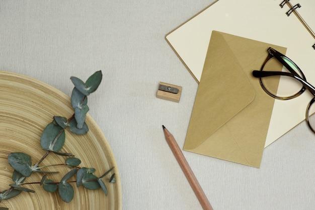 Het notitieblok, houten potlood en puntenslijper, envelop, bril, eucalyptus takken in de mand