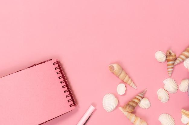 Het notitieboekje en de pen, met zeeschelpen op een roze ondergrond