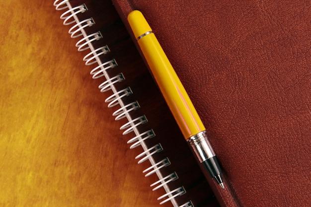 Het notitieboekje en een rode pen die op houten bureau liggen. artikelen voor kantoor en onderwijs
