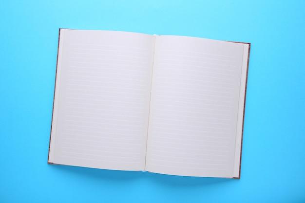 Het notitieboekje op een blauwe achtergrond, sluit omhoog
