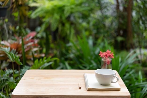 Het notitieboekje van de koffiekop, bruin potlood en mooie rode droge bloem in glasvaas op houten lijst