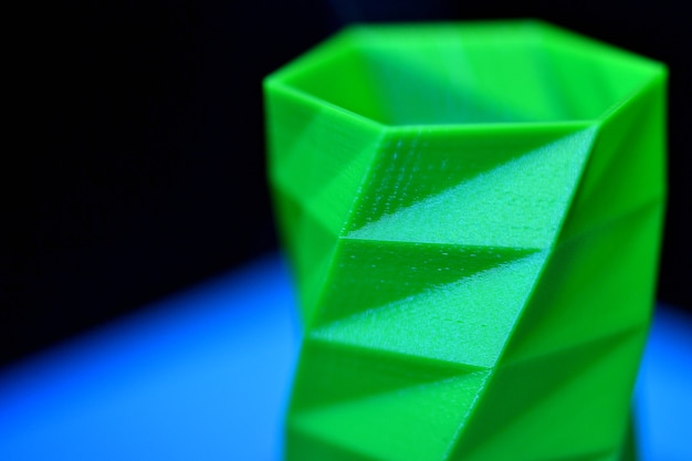Het object drukte de 3d-printer af op een blauwe en zwarte achtergrond in de 3d-printer. automatische driedimensionale 3d-printer voert plastic groene kleurenmodellering uit in het laboratorium.