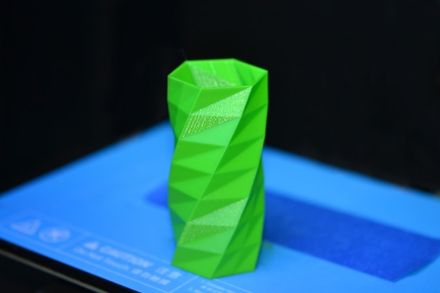 Het object geprinte 3d-printer op een blauwe en zwarte achtergrond