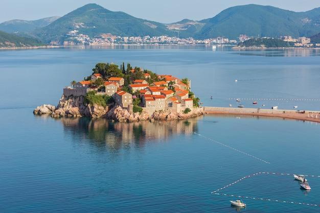 Het ochtendgezicht van het zee-eilandje sveti stefan met roze strand en stadshotel (montenegro, nabij budva)