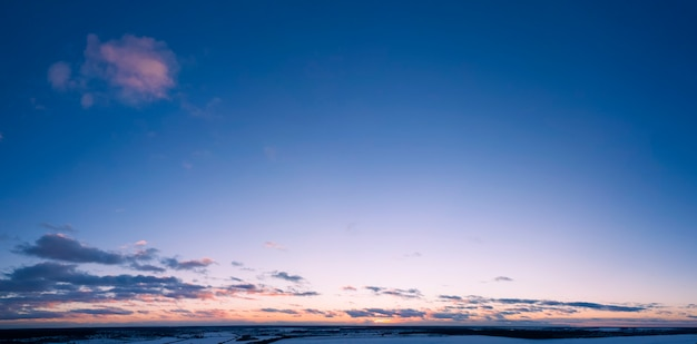Het ochtendgloren boven de wolken verlicht paars zonlicht de ochtendhemel.