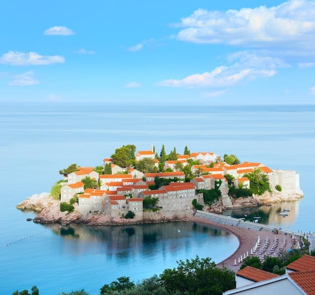 Het ochtendzicht van het zee-eilandje sveti stefan met strand en stadshotel (montenegro, 6 kilometer ten zuidoosten van budva) en een blauwe, pittoreske lucht erboven. vier schoten stikken afbeelding