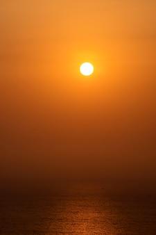 Het ochtendzonlicht reflecteert de zee en vissersboten.