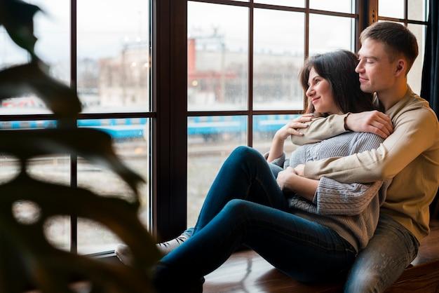 Het omhelste paar dat door venster met defocused installatie kijkt