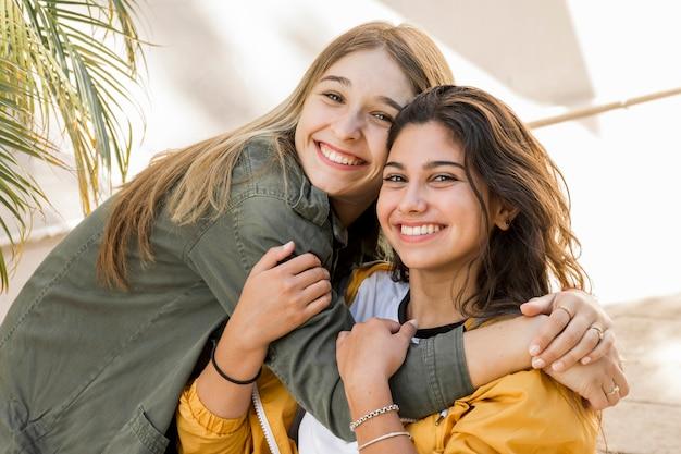 Het omhelzen van jonge vrouwelijke vrienden die camera bekijken