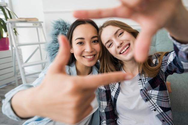 Het omhelzen van meisjes die glimlachen en fotoframe met handen zoals selfie maken