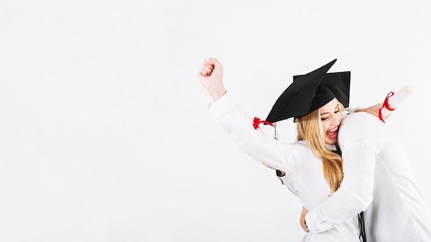Het omhelzen van paar die graduatie vieren