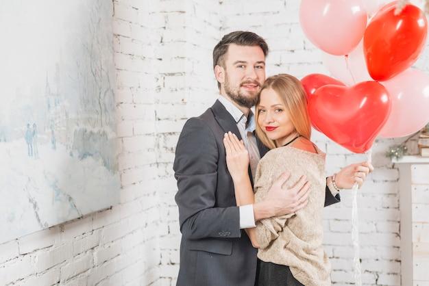 Het omhelzen van paar met bos van ballons