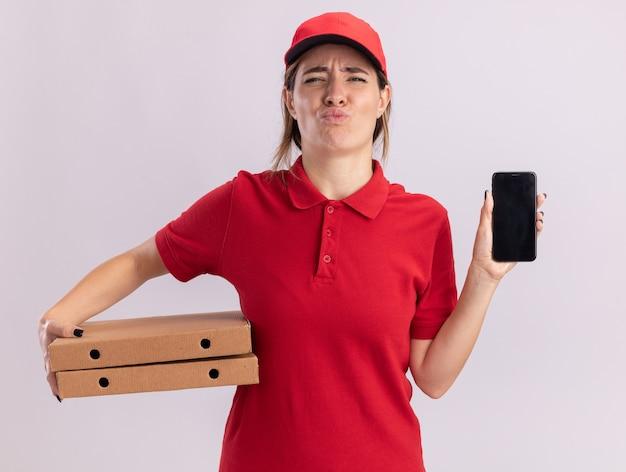 Het onaangename jonge mooie leveringsmeisje in uniform houdt pizzadozen en telefoon op wit