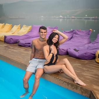Het onbezorgde minnaarspaar rust dichtbij zwembad op de achtergrond van mooie meningen van bossen, heuvels, rivier met een nevel over het