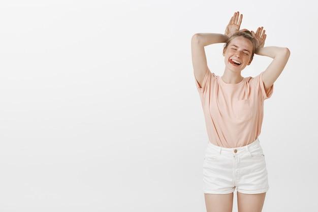 Het onbezorgde tienermeisje stellen tegen de witte muur