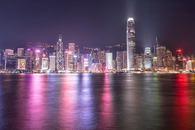 Het ongelooflijke nachtelijke stadsgezicht van lichten op het water op victoria harbour in hong kong