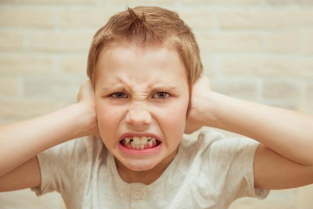 Het ongelukkige close-upportret, irriteerde de jongen, die zijn oren met zijn handen behandelt
