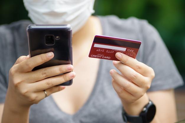 Het online winkelen met smartphone en het winkelen de leveringsdienst die van zakken als achtergrond het winkelen concept gebruiken