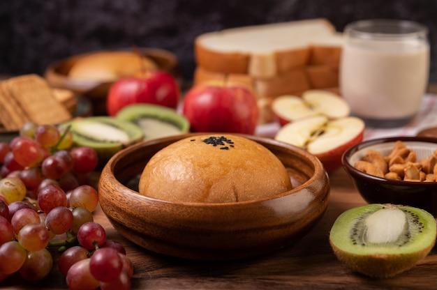 Het ontbijt bestaat uit brood, appels, druiven en kiwi op een houten tafel