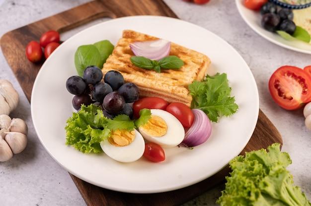 Het ontbijt bestaat uit brood, gekookte eieren, slasaus met zwarte druiven, tomaten en gesneden uien.