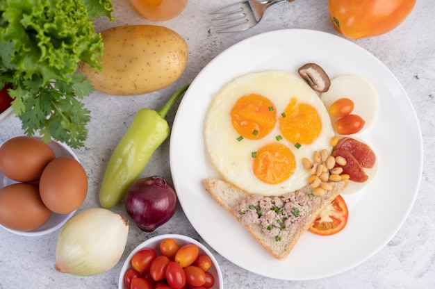 Het ontbijt bestaat uit gebakken eieren, worst, gehakt varkensvlees, brood, rode bonen en soja op een witte plaat.