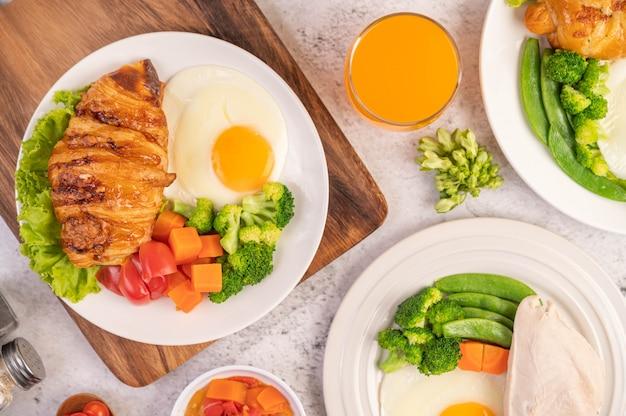 Het ontbijt bestaat uit kip, gebakken eieren, broccoli, wortelen, tomaten en sla op een witte plaat.