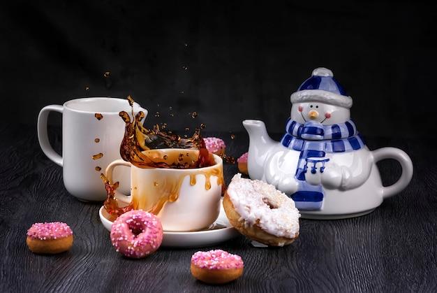 Het ontbijtconcept van kerstmis met sneeuwmantheepot met plons en dalingen van thee en roze verglaasde donuts