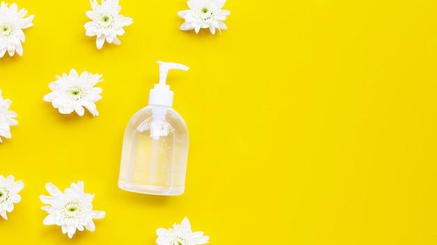 Het ontsmettingsmiddelgel van de alcoholhand in pompfles met witte chrysant op gele achtergrond.