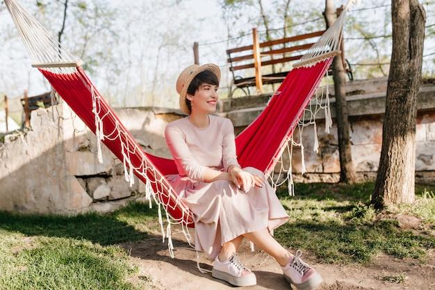 Het ontspannen donkerharige meisje met geïnspireerde gezichtsuitdrukking zit in een rode hangmat te wachten op vrienden