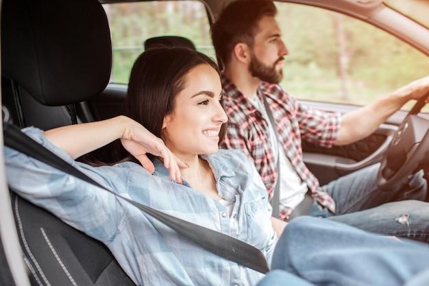 Het ontspannen en gelukkige paar zit samen en rijdt in auto. ze gebruiken de veiligheidsgordels. guy rijdt terwijl het meisje naast hem zit. ze glimlacht en kijkt recht vooruit.
