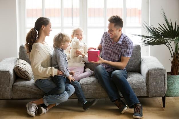 Het ontvangen van heden op het concept van de vadersdag, familiejonge geitjes die papa feliciteren