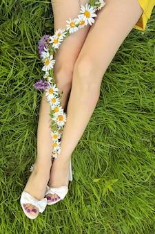 Het ontwerp van een pedicure met een matte lila coating op een meisje dat op het groene gras zit met een bloemstuk van madeliefjes aan haar voeten.