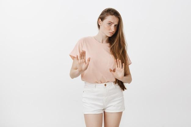 Het onwillige tienermeisje stelt tegen de witte muur