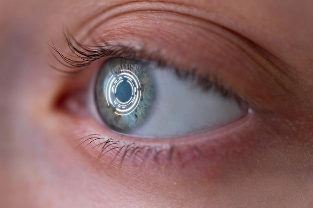 Het oog van de vrouw met slimme contactlens met digitale en biometrische implantaten om het oculaire netvlies dicht omhoog te scannen