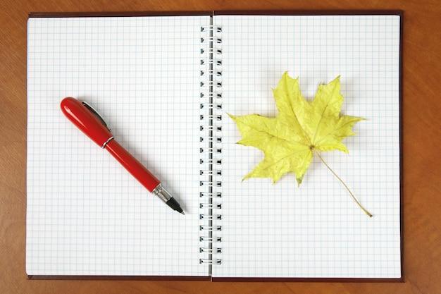 Het open notitieboekje en de rode pen met herfstblad liggend op een houten tafel