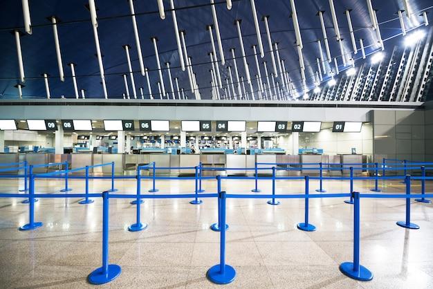 Het openbare incheckgedeelte met hindernissen voor menigtecontrole op de luchthaven in de vroege ochtend.