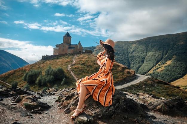 Het openlucht de donkerbruine vrouwentoerist van de reislevensstijl stellen op bergen en middeleeuwse kerk