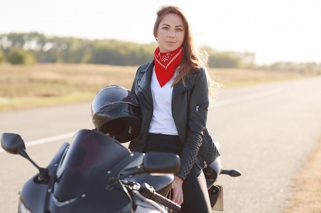Het openlucht horizontale schot van aantrekkelijke vrouw draagt rode bandana