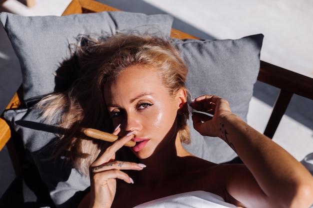 Het openluchtportret van de manier van de naakte vrouw zit op bank die zich bedekken met de sigaar van de dekenholding
