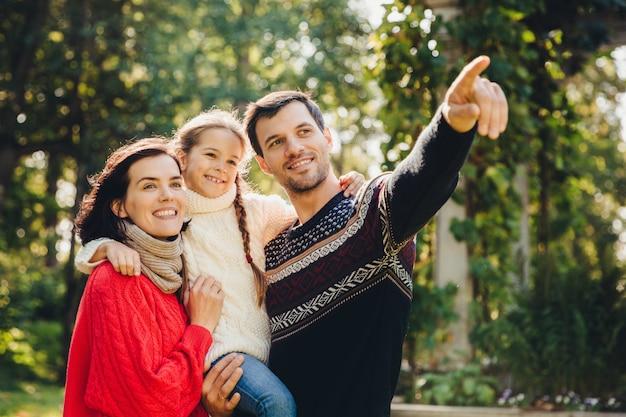 Het openluchtportret van glimlachende gelukkige vriendschappelijke familie heeft samen gang