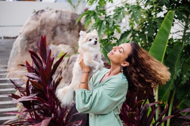Het openluchtportret van krullende europese gelooide vrouw houdt gelukkige spitz van pommeren van de huisdierenhond
