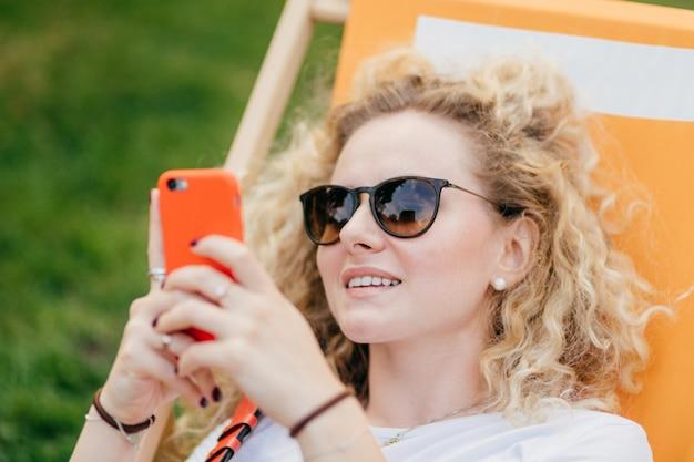 Het openluchtschot van aangenaam kijkend krullend jong wijfje in zonnebril, houdt moderne oranje slimme telefoon