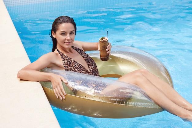 Het openluchtschot van jonge donkerbruine vrouw die met nat haar ontspannen op opblaasbaar zwemt ring, dragend manier swimwear met luipaarddruk, meisje geniet van coctails in zwembad tijdens de zomervakantie.